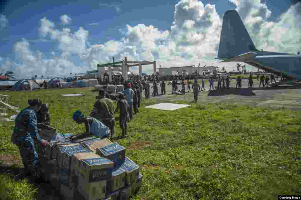 Sailors assigned to the U.S. Navy's forward-deployed aircraft carrier USS George Washington (CVN 73), Marines assigned to the 3 Marine Expeditionary Brigade (3 MEB), and Philippine civilians unload relief supplies in support of Operation Damayan. (US Navy