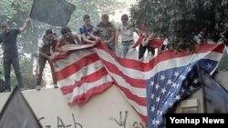 이슬람 모독 영화에 분노한 이집트 시위대가 카이로 주재 미국 대사관 앞에서 성조기를 찢고 있다(자료사진)