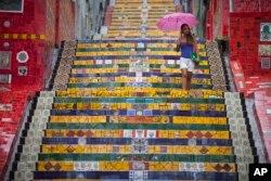 """Seorang perempuan menuruni tangga yang didekorasi oleh seniman Chili Jorge Selaron, """"Selaron Stairway"""" di Rio de Janeiro, Brazil, 10 Januari 2013. (REUTERS)"""
