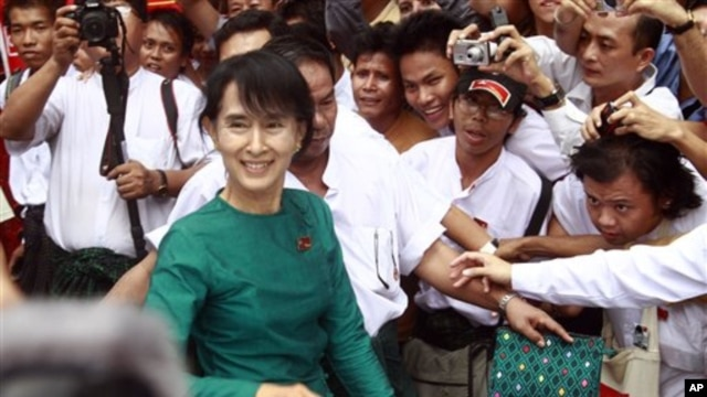 Burma's pro-democracy leader Aung San Suu Kyi greets supporters as she leaves her National League for Democracy party following her meeting with newly elected lawmakers at the party headquarters in Rangoon, April. 7, 2012.