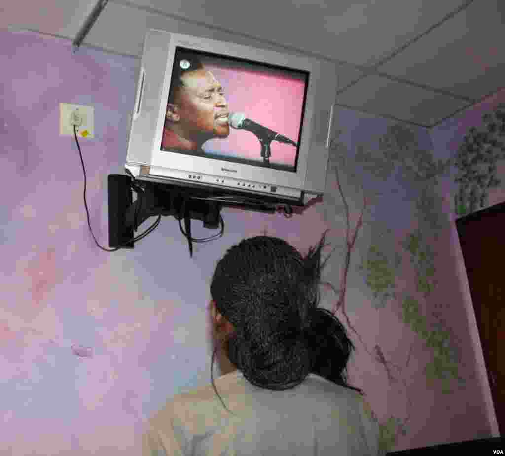 In a pediatric ward, a 16-year-old with HIV and multi-drug resistant tuberculosis who battles to talk and to breathe watches television. She plans to become a doctor who will help others.(Photo by Darren Taylor)