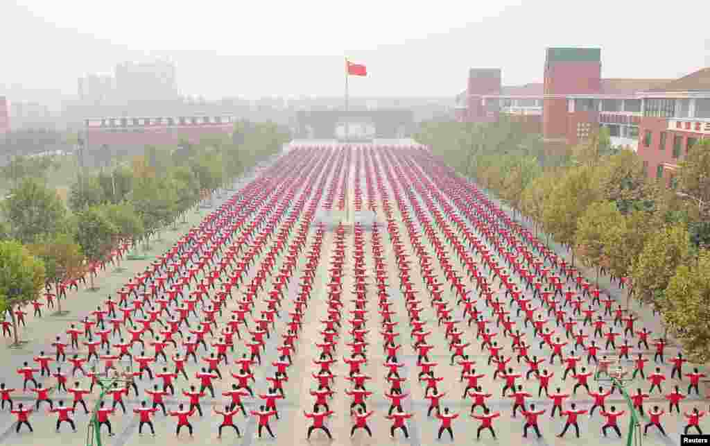 A Chinese national flag flies as students practice Taichi on a playground of a high school, during a Guinness World Record attempt of the largest martial arts display, on a hazy day in Jiaozuo, Henan province, China, October 18, 2015.