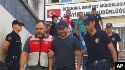 土耳其流行音乐明星阿提拉•塔斯(中)被警察押送到警察局。