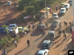 FILE - In this image made available by Malikahere.com security personnel, right, arrive close to the scene of an attack on a hotel in Bamako, Mali, Nov. 20, 2015.