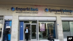 A man (L) makes a transaction at an ATM machine outside an Emporiki Bank branch in Athens, March 9, 2012.