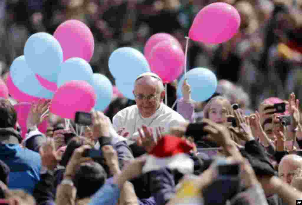 Pope Francis passes among the faithful after celebrating his first Easter Mass in St. Peter's Square at the Vatican, Sunday, March 31, 2013. Pope Francis made an Easter Sunday peace plea, saying conflicts have lasted too long in Syria, and between Israel