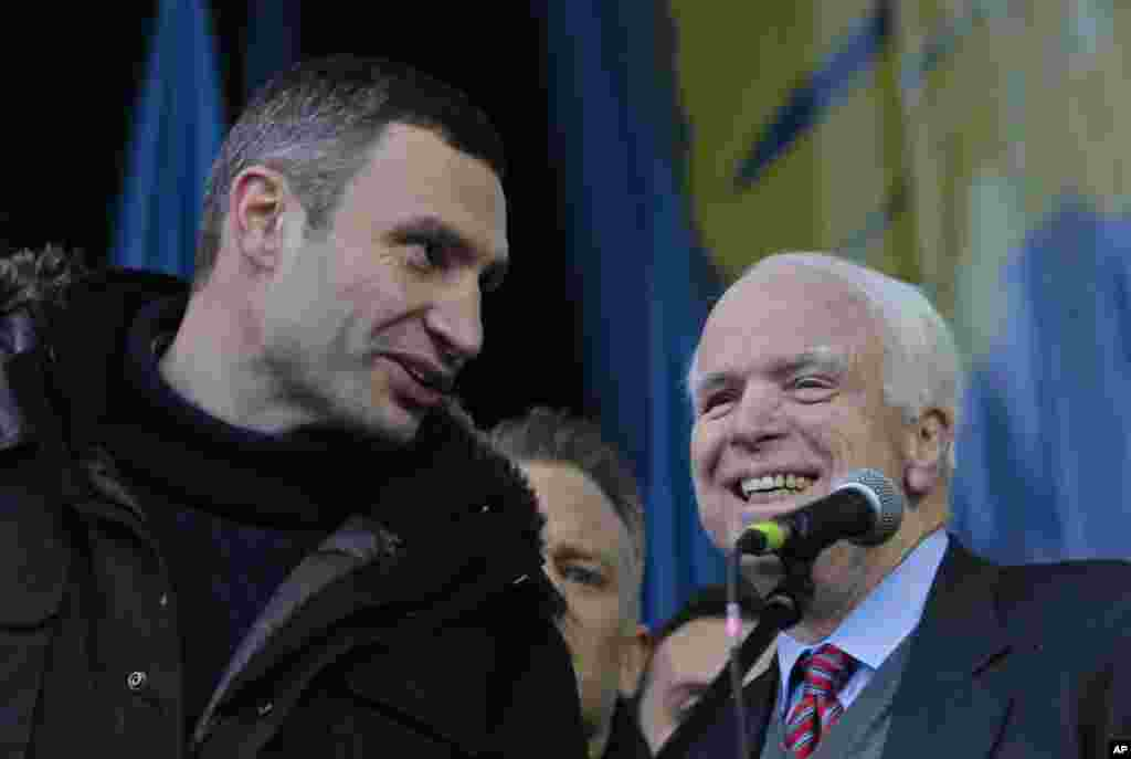 Ukrainian lawmaker and chairman of the Ukrainian opposition party Udar (Punch), WBC heavyweight boxing champion Vitali Klitschko, left, speaks to U.S. Senator John McCain during a pro-European Union rally in Independence Square, Kyiv, Ukraine, Dec. 15, 2013.