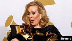 FILE - Singer Adele holds her six Grammy Awards at the 54th annual Grammy Awards in Los Angeles, California February 12, 2012.