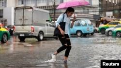 A woman walks on a flooded street in Bangkok, Thailand, Sept. 24, 2018.