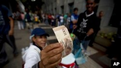 Seorang pedagang memeriksa keaslian uang kertas lembaran 100 bolivar, sementara warga antri untuk menukar uang di sebuah bank di Caracas, Venezuela, 13 Desember 2016. (AP Photo/Fernando Llano)