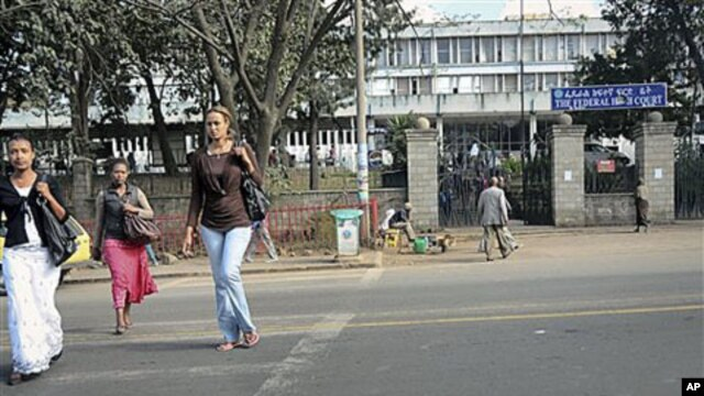 Pedestrians walk past the Federal High Court building housing a terror trial against two Swedish journalists, Johan Persson and Martin Schibbye, in Addis Ababa, Ethiopia, November 1, 2011.