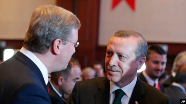 Turkish Prime Minister Tayyip Erdogan, right, talks with EU enlargement commissioner Stefan Fuele, Istanbul Conference of the Ministry For EU Affairs, Istanbul, June 7, 2013.