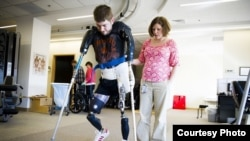 Former Marine Sgt. John Peck is seen walking on artificial limbs before having a double arm transplant. (Photo: Courtesy John Peck)