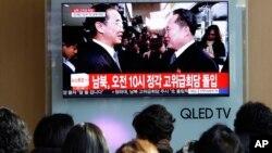 Personas observan una pantalla de TV mientras el ministro de Unificación de Corea del Sur (izquierda) saluda a su contraparte del Norte.