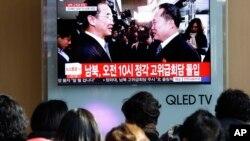 Des Coréens regardent le ministre sud-coréen Cho Myoung-gyon, à gauche, avec Ri Son Gwon, chef de la délégation nord-coréenne, le 9 janvier 2018.