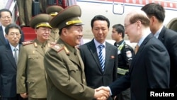 Choe Ryong-Hae, left, director of the General Political Bureau of the Korean People's Army (KPA) of North Korea, shakes hands with Chinese official upon arrival at the airport, Beijing, May 22, 2013.