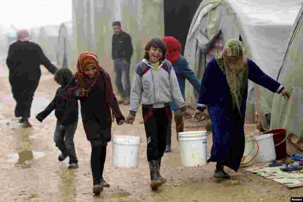 Internally displaced people carry buckets of water as they walk during the cold weather in Jerjnaz camp, in Idlib province, Syria.