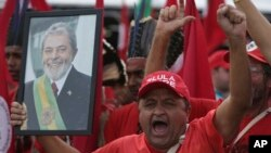 A supporter holds a photo of Brazil's jailed former president, Luiz Inacio Lula da Silva, as he takes part in the Free Lula March, in Brasilia, Aug. 15 2018.