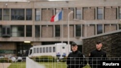 FILE - French gendarme stand in front of the entrance of the Fleury-Merogis prison near Paris, France. The prison is home to Salah Abdeslam.