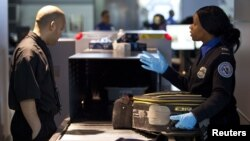In this 2012 file photo, a Transportation Security Administration (TSA) security agent checks a traveler's luggage at John F. Kennedy Airport in New York. (REUTERS/Andrew Burton)