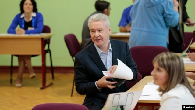 Current Moscow mayor Sergei Sobyanin (C) fills out his ballot before voting at a polling station in Moscow September 8, 2013.