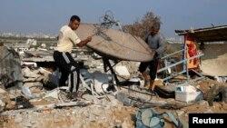 Người Palestine khiêng một vệ tinh ra khỏi đống đổ nát của một căn nhà ở làng Johr El-Deek, Dải Gaza, ngày 17/8/2014.