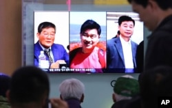 FILE - People watch a TV news report on screen, showing portraits of three Americans, Kim Dong Chul, left, Tony Kim and Kim Hak Song, right, detained in the North Korea, at the Seoul Railway Station in Seoul, South Korea, May 3, 2018.