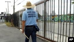 Một thanh tra viên của hạt Dade tìm kiếm các vũng nước đọng tại một bãi đất trống ở Miami, Florida, ngày 2/8/2016.