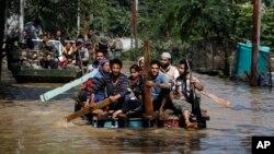 Warga Kashmir menggunakan rakit untuk menyelamatkan warga yang terkena musibah banjir di Srinagar, wilayah Kashmir yang dikuasai India (10/9). Pihak berwenang mengatakan banjir yang melanda India dan Pakistan ini telah menewaskan lebih dari 440 jiwa.