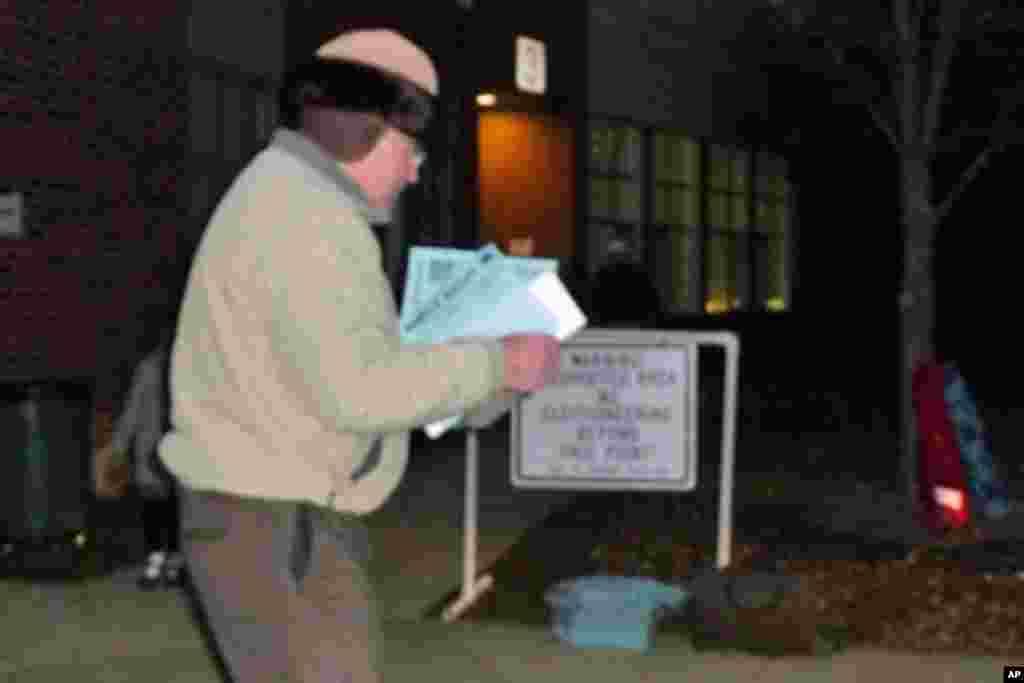 政党党工一大早在投票站外准备传单