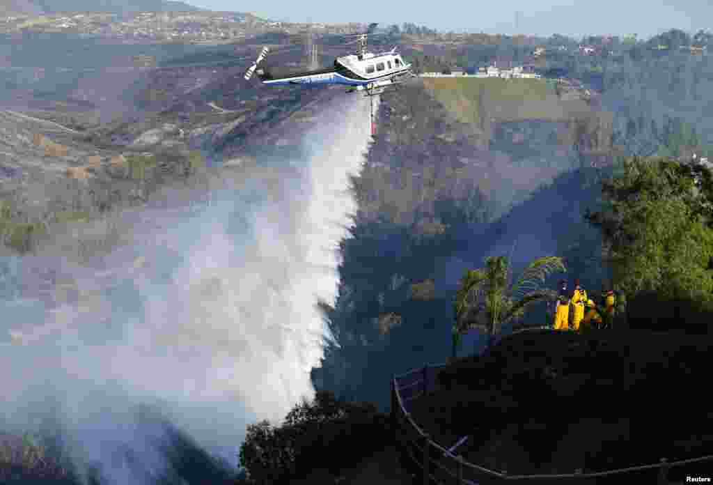 A helicopter drops water on a burning hillside next to homes as firefighters battle the Bernardo Fire, north of San Diego, California, May 13, 2014. More than 20,000 homes and other residences were being evacuated in and around San Diego as a fast-moving, fire and county officials said.
