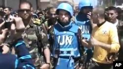 Foto ini diambil dari video amatir yang dirilis oleh kantor berita Shaam (22/4): seorang tentara pembebasan Suriah mendampingi pemantau PBB di kota Rastan, Homs.