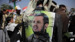 A Supporter of Houthi Shiites displays a poster of Abdel-Malek al-Houthi, the leader of Yemen's Shiite rebels, on his jacket during a rally to mark the third anniversary of the Houthis' takeover of the Yemeni capital, in Sanaa, Yemen, Sept. 21, 2017.
