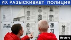 Ljudi gledaju poternice za osumnjičenim teroristima na oglasnoj tabli u četvrti Adler u Sočiju, gde se od 7. do 23. februara održavaju Zimske olimpijske igre