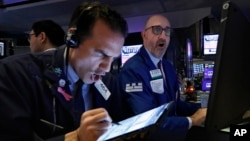 Trader Gregory Rowe, left, and specialist Peter Giacchi work on the floor of the New York Stock Exchange, Thursday, March 12, 2020.
