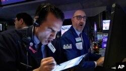 Para pialang di New York Stock Exchange hari Kamis (12/3). Indeks bursa New York kembali anjlok lebih dari 2.000 point dan tercatat pada 21.450 menjelang tutup pasar.