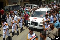Egyptian policemen march with a vehicle carrying the body of their comrade, killed Monday in Cairo outside Republican Guard headquarters in an incident that left 51 people dead, at his funeral in Alexandria, July 9, 2013.