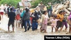 Warga masyarakat desa Rogo, Dolo Selatan, Kabupaten Sigi, Sulawesi Tengah berjalan kaki di jalan raya yang terendam air banjir bandang yang menyebabkan 70 rumah terendam dan 200 jiwa mengungsi, 15 September 2020. (Foto: VOA/Yoanes Litha)