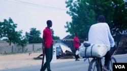 Un cycliste roule sur son vélo à côté des membres de la Force conjointe civile qui patrouillent dans les rues à la recherche de combattants de Boko Haram, à Maiduguri, Nigeria, juin 2016. (C. Oduah pour VOA)