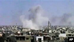Trong bức ảnh trích từ video của một người quay phim nghiệp dư, khói bốc lên từ khu vực bị trúng đạn pháo, trong thành phố Homs