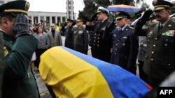 Commanders of the Police and Armed Forces of Colombia salute by the coffin of lieutenant colonel Alfredo Ruiz next to his wife Daissy Esperanza (2-L) during his funeral in Bogota, Colombia, on June 14, 2015.