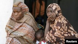 Women sit with their children at a camp for internally displaced people in Nigeria's central city of Jos.