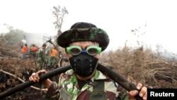 Tentara Indonesia menggunakan kacamata renang untuk melindungi matanya dari asap saat membantu memadamkan kebakaran hutan di desa Parit Indah, Kampar, Riau (8/9). (Reuters/YT Haryono)
