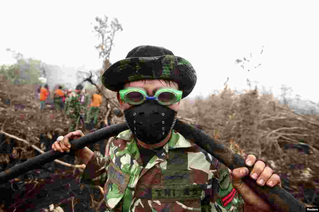 An Indonesian soldier uses swimming goggles to protect his eyes from smoke while helping to fight a fire in a peatland forest area in Parit Indah Village, Kampar, Riau province, Indonesia.