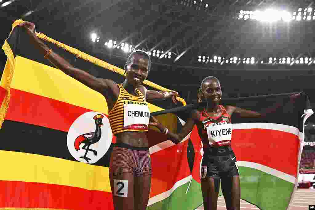 Uganda's Peruth Chemutai, left, and Kenya's Hyvin Kiyeng celebrate after Chemutai won gold and Kiyeng won silver in the women's 3,000-meter steeplechase final at the 2020 Summer Olympics in Tokyo, Japan, Wednesday, Aug. 4, 2021. (Ben Stansall/Pool Photo via AP)