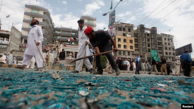 Rescue workers collect shattered glass from the site of a bomb blast on University Road in Peshawar, April  29, 2013.