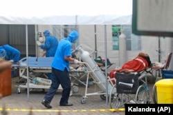 Seorang petugas medis mendorong tangki oksigen yang akan digunakan untuk merawat pasien di tenda darurat yang didirikan untuk menampung lonjakan kasus COVID-19, di RSUP Dr Sardjito Yogyakarta, Minggu, 4 Juli 2021. (AP Photo/Kalandra)