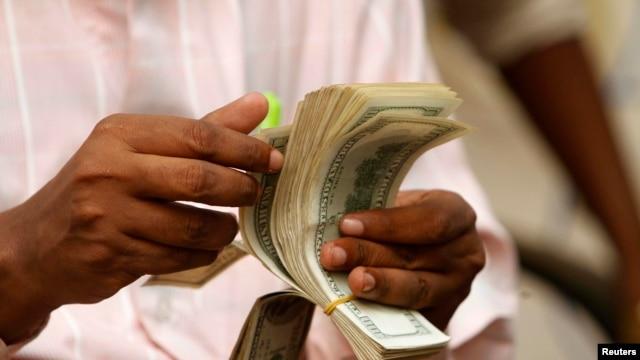 "FILE - A Somali man counts his money at a Dahabshiil money transfer office in ""Kilometer Five"" street of Soobe village, southern Mogadishu, May 8, 2013."