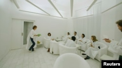 FILE - In Sweden, where lack of winter sunlight can contribute to depression, customers dressed in white robes take in simulated sunlight at Stockholm's Iglo Ljuscafe, Dec. 12, 2006.