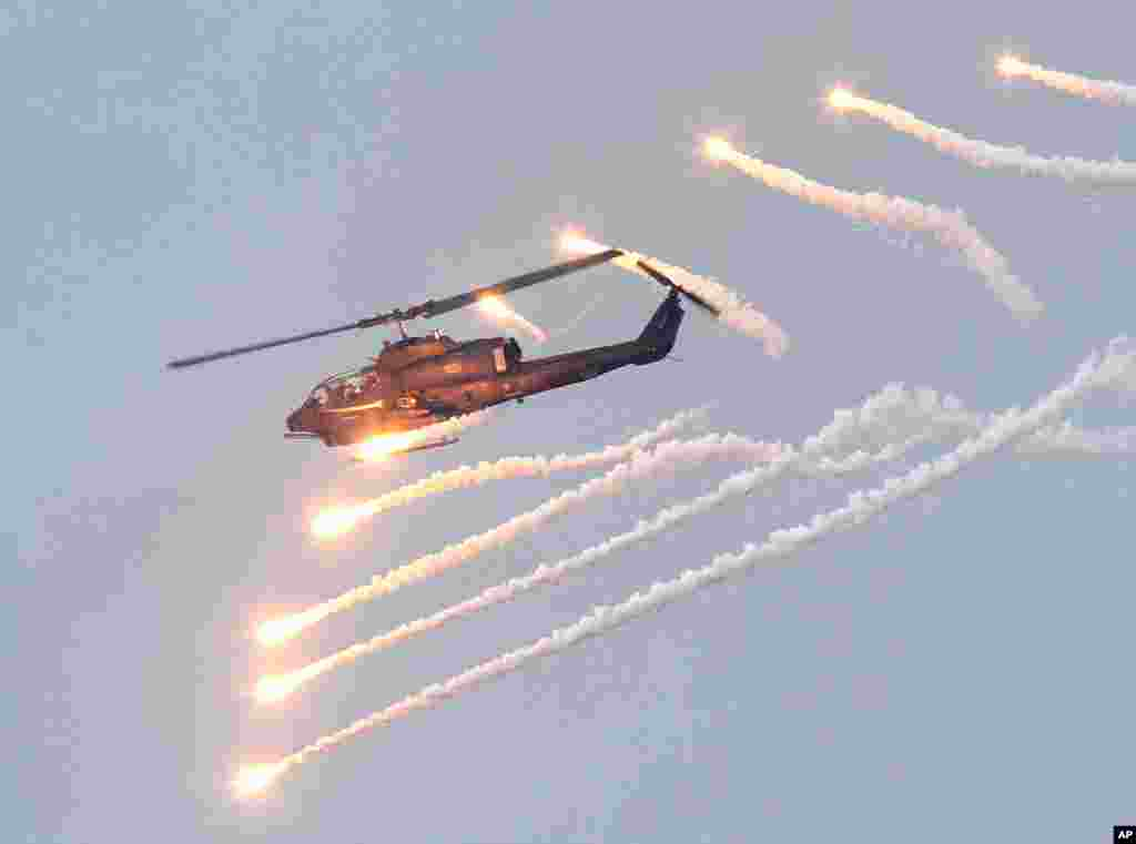 An AH-1W attack helicopter launches flares during Han Kuang military exercises in Penghu county, Taiwan, April 17, 2013.